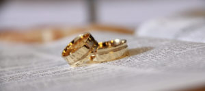 Two gold wedding bands on top of a book